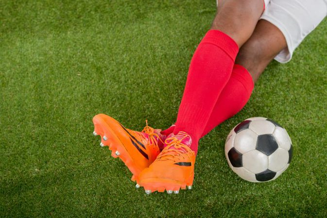 legs of soccer player with soccer ball