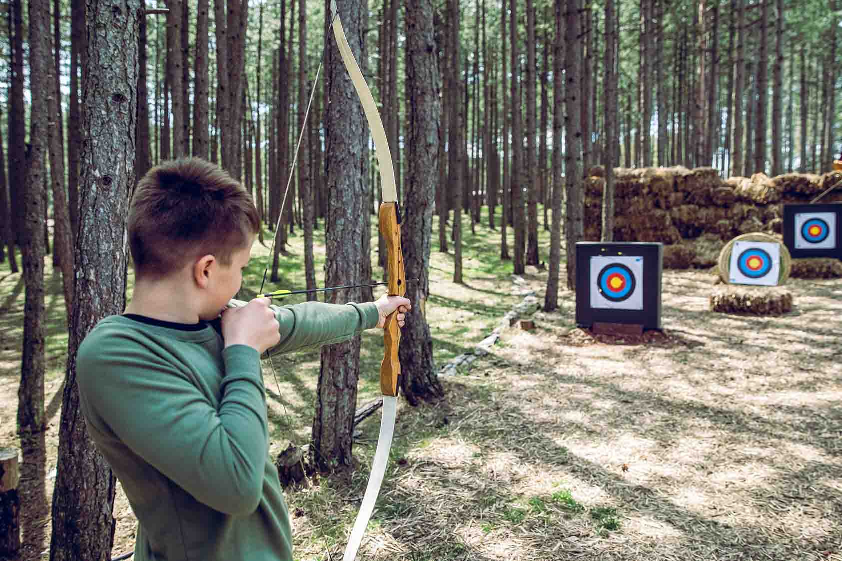 teen boy learning archery at an outdoor park, aiming at a target
